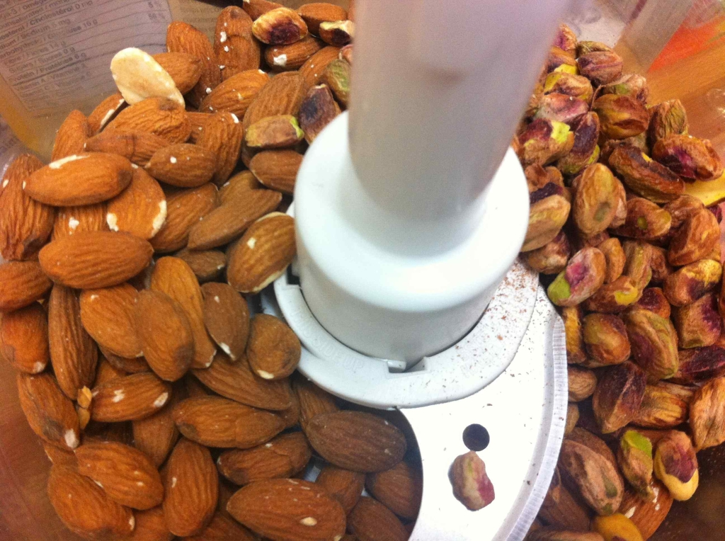 Meanwhile, I added 1/2 cup almonds and 1/2 cup pistachios (both raw) to the bowl of my food processor.