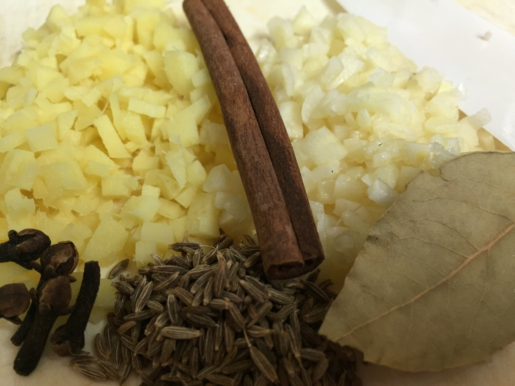 """I chopped 5 cloves of garlic and a 3"""" piece of ginger. I measured out 5 cloves, 1 tbsp. cumin seeds a cinnamon stick and 1 bay leaf."""